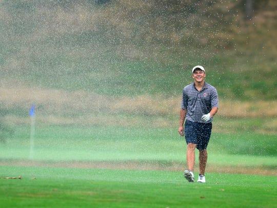 Golfer Luke Hoffnagle walks through a sprinkler on