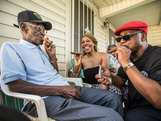Richard Overton, left,  smokes a cigar with a few neighborhood