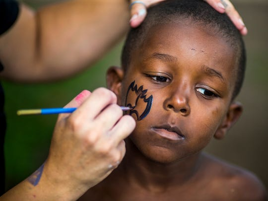 Nina Boyd, of Over the Line Productions, paints the face of Jamarcus Walker, 5, at the 4th Annual Taste of OTR at Washington Park Saturday, August 27, 2016.