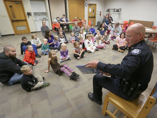 Indianola Police Chief Dave Button reads a book to children last year during the Booked by a Cop literacy program at the Indianola Public Library.
