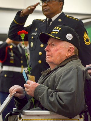 CPL Nolan E Simpson looks at the crowd while taps play. Behind, Sgt.First Class William Vanhook Jr. salutes the flag.
