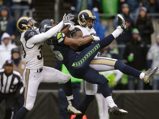 St. Louis Rams' Trumaine Johnson, right, intercepts a pass meant for Seattle Seahawks' Tyler Lockett, center, as Cody Davis follows in the first half of an NFL football game, Sunday, Dec. 27, 2015, in Seattle. (AP Photo/Stephen Brashear)
