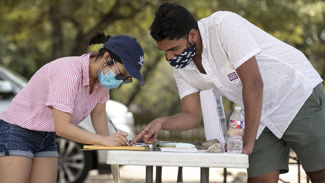 Saatvik Ahluwalia, right, helps Quynhanh Tran fill out a Texas voter registration application during a census and voter registration information session hosted by the Asian Democrats of Central Texas at the Asian American Cultural Center last month. Central Texas officials are urging residents to respond to the U.S. Census Bureau by this year's deadline of Sept. 30.