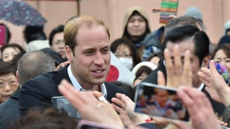 Prince William is greeted by Japanese well-wishers as he visits a hilltop to look over significant land clearance caused by the 11 March 2011 earthquake and tsunami.