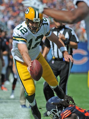 Green Bay Packers quarterback Aaron Rodgers (18) stretches for yardage on a fourth quarter scramble against the Chicago Bears at Soldier Field.
