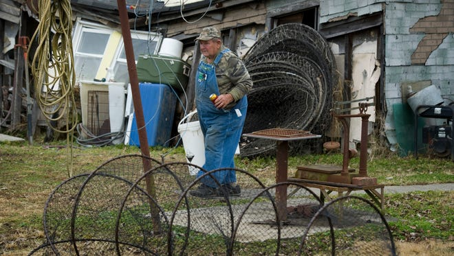 """Hubert """"Pee Wee"""" Clifford makes his way to his New Haven, Ill., workshop to continue his nut-cracking duties Tuesday afternoon. The retired fishing net knitter, mechanic and fisherman supplements his income by collecting and shelling pecans."""