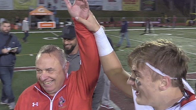 Defensive coach for Bergen Catholic Greg Toal is declared the winner at the end of the game celebration by Bergen Catholic quarterback Johnny Langdon.