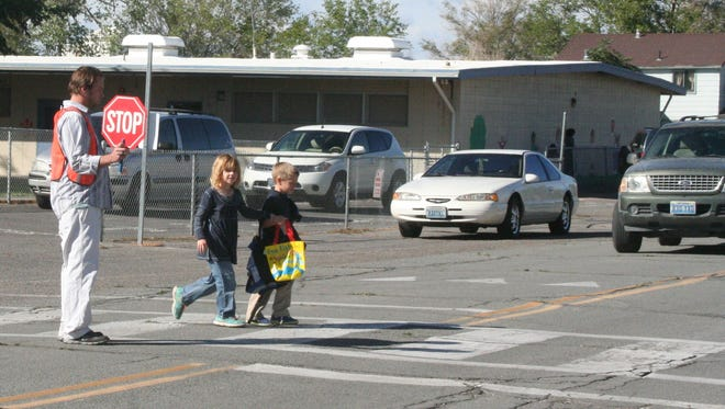 A crossing guard stops traffic to let children cross the street in the crosswalk in front of Fernley Elementary School on Hardie Lane Monday.
