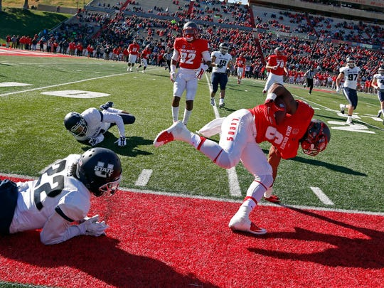 New Mexico running back Jhurell Pressley, right, looses his balance after being defended by Utah State cornerback Bryant Hayes (22) during the first half of an NCAA college football game in Albuquerque, N.M., Saturday, Nov. 7, 2015. New Mexico won 14-13.