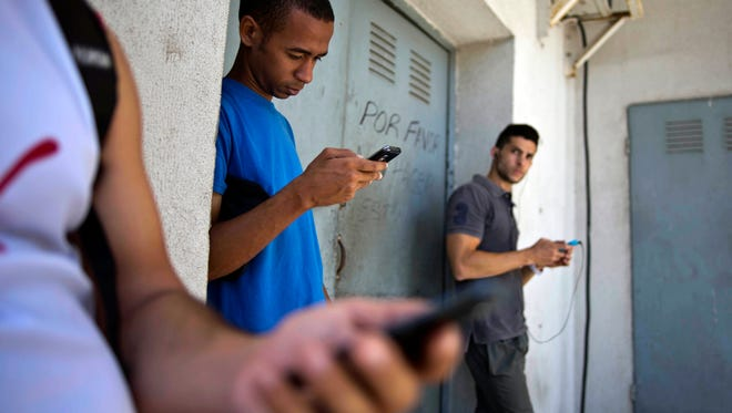 Students gather behind a business looking for a Internet signal for their smart phones in Havana, Cuba, on April 1, 2014.
