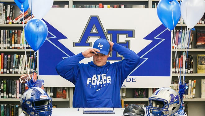 McNary High School senior Kolby Barker puts on his Air Force cap as he signs his commitment to play football for the United States Air Force Academy on Wednesday, Feb. 1, 2017.