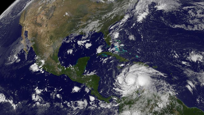A satellite image shows Hurricane Matthew (lower right) spinning in the Caribbean Sea on Sunday, October 2, 2016.