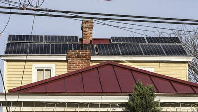 Solar panels are shown on the roof of a yellow house at 173 William Street in Clifton.