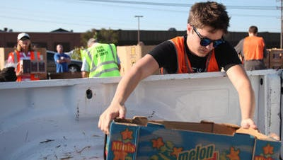 A volunteer loads food at a Second Harvest Food Bank Tailgate.