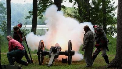 Confederate Civil War reenactors fire a cannon as Mosinee celebrates pioneers of north-central Wisconsin at Little Bull Falls LogJam in 2013.