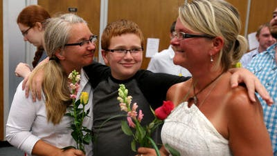 Aiden Murphy, 11, smiles as his mothers Kimberly Trojan, left, and Jackie Cornell wait in a large crowd for their marriage license inside the City County Building, Wednesday, June 25, 2014.