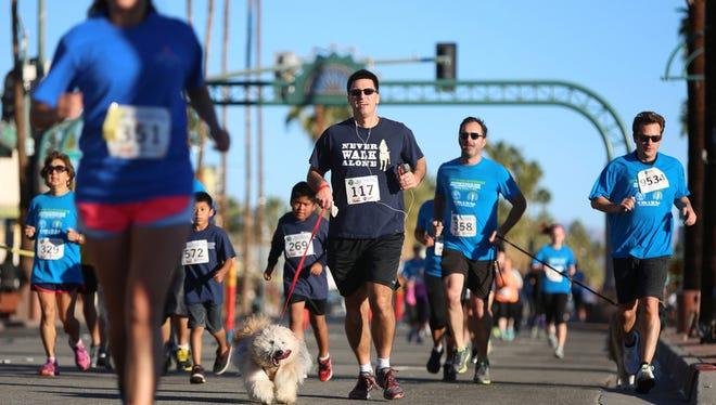 01/17/15 Taya Gray, Special to The Desert SunRunners and dogs run down Palm Canyon Drive in Palm Springs during the Mayor's Healthy Planet Healthy You 5K Race on Saturday, January 17, 2015.