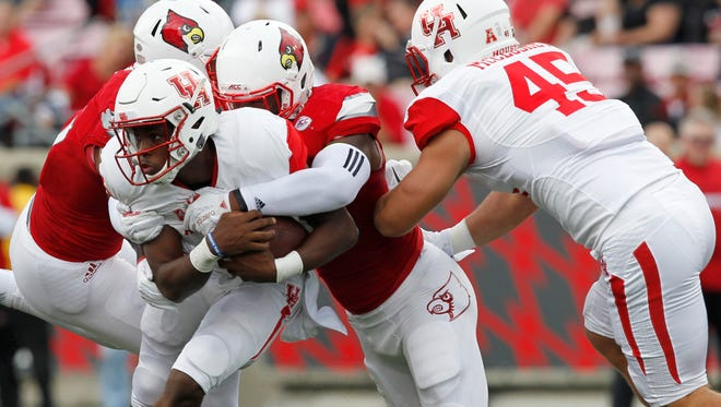 University of Houston quarterback Greg Ward  (1) is tackled by University of Louisville's Keith Kelsey (55) during the first half of play at Papa John's Stadium in Louisville, Kentucky.       September 12, 2015
