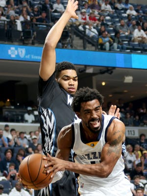 Memphis Grizzlies Mike Conley, right,  looks to pass defended by Minnesota Timberwolves Karl-Anthony Towns, left.