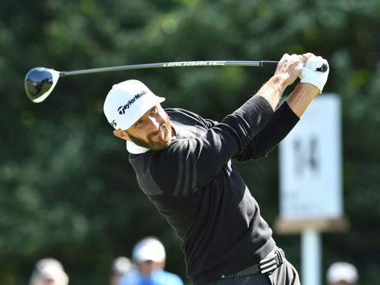 Dustin Johnson hits his tee shot on the 14th hole during