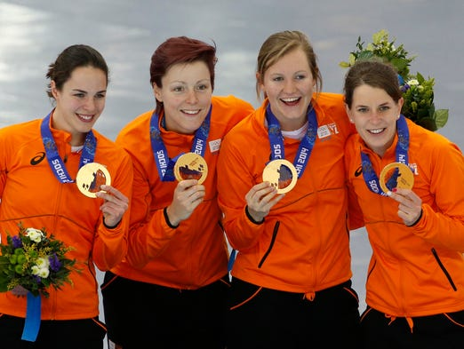 Gold medalists from the Netherlands celebrate their victory in speed skating ladies' team pursuit.