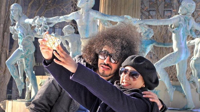 Temperatures in the upper 30s in Downtown Indianapolis brought people outdoors today in advance of a winter storm. Visiting students from Saudi Arabia, Faisal Alfarstloti (left) and Fatima Alawami snap a selfie at the base of the fountain in University Park, near Pennsylvania and New York streets. It was a sunny 37 degrees.