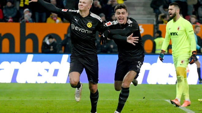Dortmund's Erling Haaland, left, celebrates with Giovanni Reyna after scoring a goal in a German Bundesliga soccer match between FC Augsburg and Borussia Dortmund in Augsburg, Germany, Saturday, Jan.18, 2020.