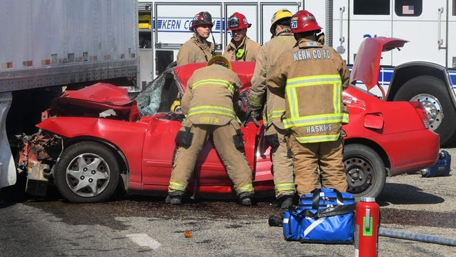 Firefighters work to free woman from car that collided with truck on Highway 33 at Cadet Road