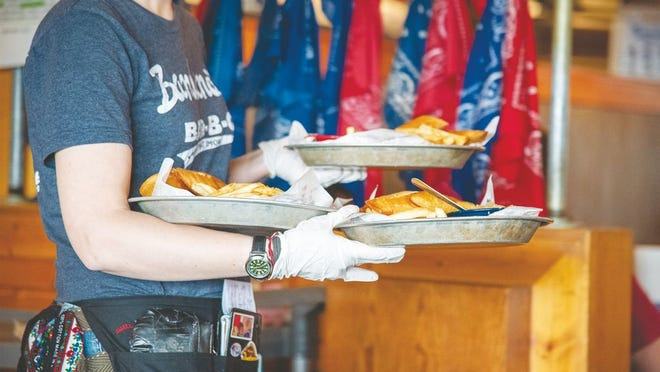 A server brings out plates of food at Bandana's in Osage Beach.
