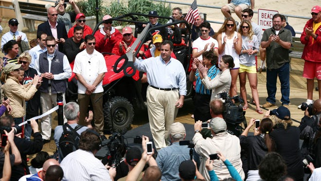Gov. Chris Christie wielding giant scissors on the Asbury Park boardwalk to kick off Memorial Day weekend on May 23, 2014. He's back at the Shore in advance of another holiday weekend today. (Governor's Office/Tim Larsen)