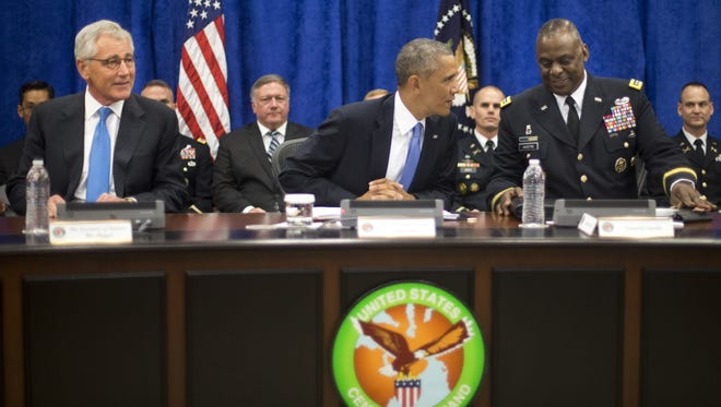 In this Sept. 17, 2014 photo, President Barack Obama, center, with Sec. of Defense Chuck Hagel, left, and Gen. Lloyd J. Austin III, right, Commander of the US Central Command (CentCom), before the start of a briefing at MacDill Air Force Base, Fla.  Obamaís military campaign against Islamic State extremists has already crept beyond the narrow parameters he first outlined three months ago.  But military experts both inside and outside of the administration argue that even more may be needed for the mission to succeed, including embedding U.S. ground troops with Iraqi security forces who are on the front line of the fight against the violent militants.