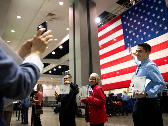 In this Wednesday, Feb. 15, 2017, file photo, Erik Danialian, a 21-year-old immigrant from Iran, poses with his U.S citizenship certificate in front of a large U.S. flag after a naturalization ceremony at the Los Angeles Convention Center, in Los Angeles.