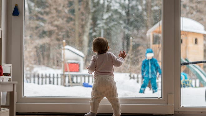 Little baby standing at a large view window watching a sibling outdoors playing in thick winter snow in the garden with forest backdrop.