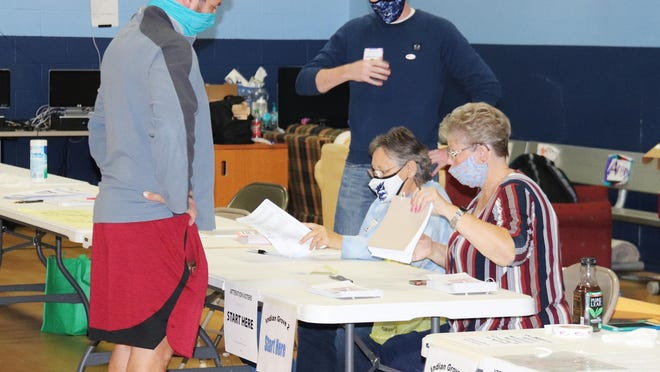 Election judges look over information as a voter signs in before making his selections Tuesday at the Boys & Girls Club in Fairbury.