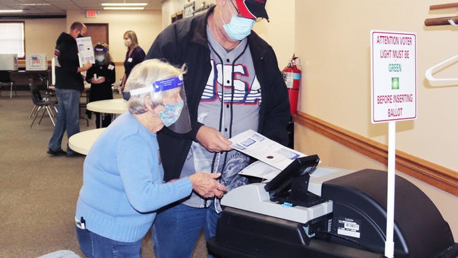 Election judge Carol Howells, left, helps Gary Barnes place his voting sheet into the machine Tuesday morning. Turnout was rather heavy in the county in the morning hours. Final election results will not be known until later this week.