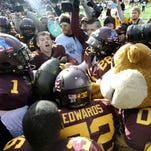 Minnesota players and mascot Goldy hoist the Floyd of Rosedale trophy after their Nov. 8, 2014, win against Iowa in Minneapolis.