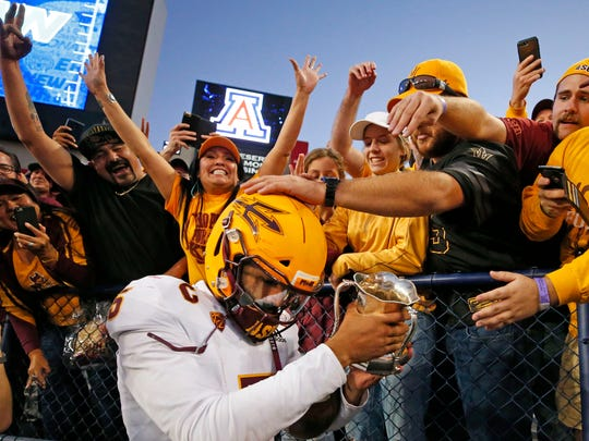 Arizona State Sun Devils quarterback Manny Wilkins (5) takes the Cup to the fans after defeating Arizona Wildcats during the Territorial Cup football game at Arizona Stadium in Tucson on Nov. 24, 2018.