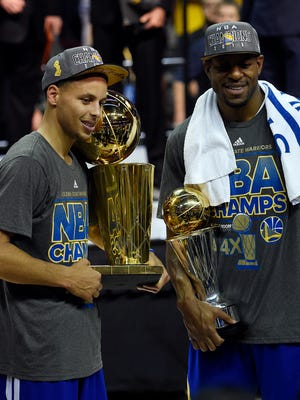 Warriors guard Stephen Curry poses with the Larry O'Brien Trophy as Andre Iguodala celebrates with the NBA Finals MVP trophy.