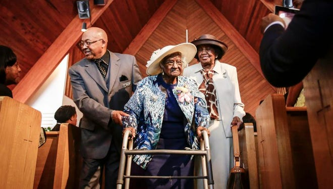 Deacon Charles Smith, left, and church charter member Willa Williams, right, help escort Jeralean Talley, who turned 115 years old, to the reception in her honor at the New Jerusalem Baptist Church in Inkster, Mich., on May 25, 2014.