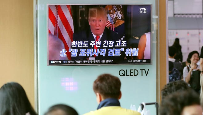 People watch a TV screen showing a local news program with an image of U.S. President Donald Trump, at Seoul Train Station in Seoul, South Korea earlier this month.