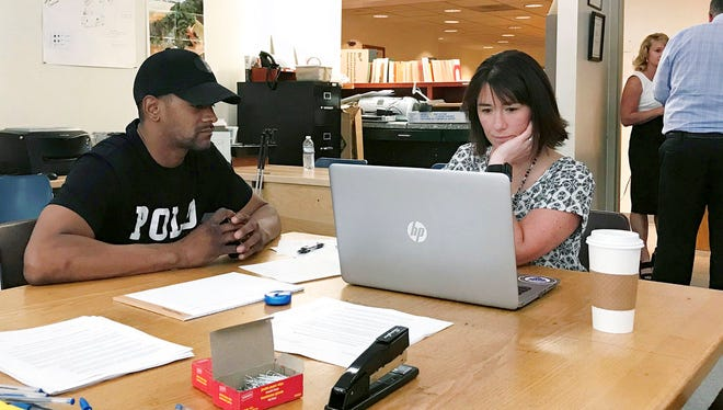 In this June 12, 2018, photo, Steven Martin, left, works with Chittenden County State's Attorney Sarah George in Burlington, Vt., on paperwork to remove a minor marijuana conviction from his record.