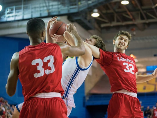 Delaware guard Ryan Daly gets tied up with between Cornell defenders Stone Gettings (left) and Jack Gordon on Dec. 28, 2017.