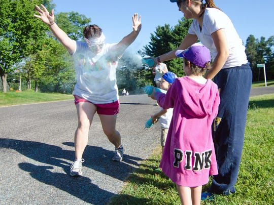 Runners are covered in dyed cornstarch during the Color Out Cancer run at the Leila Arboretum Saturday morning.