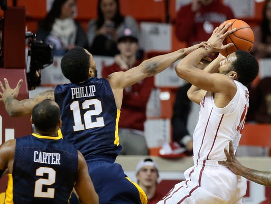 Oklahoma guard Jordan Woodard, right, is fouled by West Virginia guard Tarik Phillip (12) during the first half of an NCAA college basketball game in Norman, Okla., Wednesday, Feb. 8, 2017. (AP Photo/Sue Ogrocki)