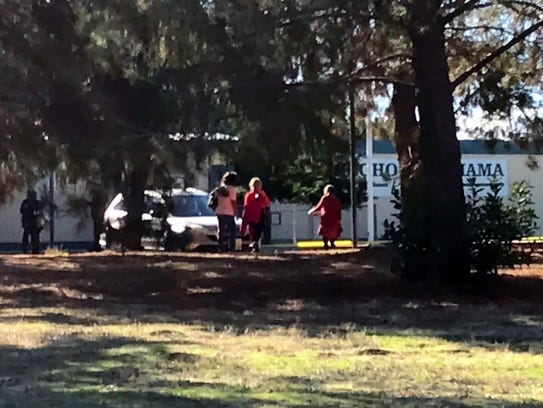 Adults stand outside Rancho Tehama Elementary School