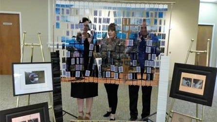 Jana Pryor, Julie Keirle and Rob Cook peer from The B Side of their upcoming exhibit at the John McIntire Library.