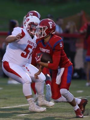 Fairport's Quarterback Mike Pellittiere, after faking a hand-off ,gets by Penfield's Ryan Long.