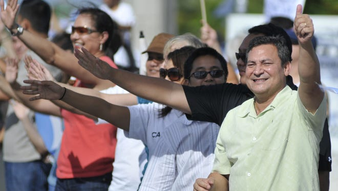 In this file photo, then-Sen. Eddie Calvo and his supporters wave to passing motorists along Route 1 in Dededo.