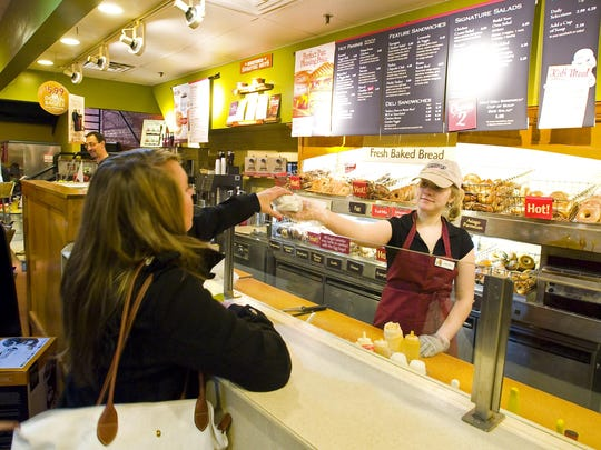 Britany Fitzgerald of South Burlington serves up a bagel to a customer at the Bruegger's bagel store on Church Street in Burlington on Monday, November 8, 2010.