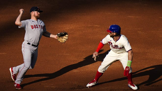 Red Sox second baseman Christian Arroyo, left, throws to first base past the Phillies' Bryce Harper on a groundout by J.T.